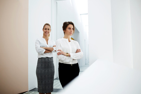 formal wear: Two female successful reliable colleagues in formal wear standing with crossed arms in hallway of company, young women leaders posing in modern office interior looking authoritatively and confidently