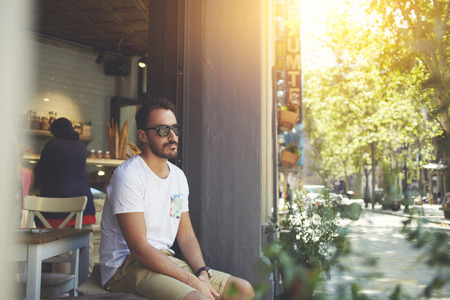 restaurateur: Young businessman in sunglasses looking on copy space while relaxing near modern bakery shop in sunny day, young rich male thinking about something while sitting on window of comfortable restaurant Stock Photo