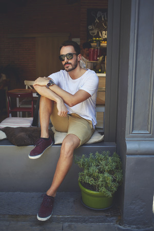 restaurateur: Professional business owner with trendy look resting after meeting with partners in modern cafe, man millionaire dressed in casual clothes and branded sunglasses sitting on windowsill of own cafe Stock Photo