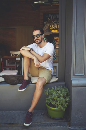 restaurateur: Skilled male employer dressed in daily clothes and stylish sunglasses enjoying free time in summer season, confident happy businessman sitting on windowsill of modern restaurant during work break Stock Photo