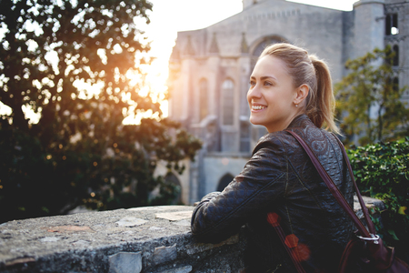 Young smiling woman traveler enjoying town landscape while standing outdoors against big old church, cheerful hipster girl with a rucksack on her back looking at beautiful places from balcony outdoors