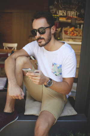 Successful man restaurateur in stylish sunglasses waiting for a call on mobile phone while sitting in healthy bar, confident male with trendy look holding cell telephone in hand during rest in cafe Stock Photo