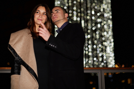 beguin: Caring husband showing something to his wife while walking together outside during their honeymoon, loving couple consider something while standing outdoors during the celebration of Valentines Day