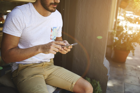 Cropped shot view of hipster guy reading text message on cell telephone while sitting outdoors in summer season, young bearded man dressed in casual clothes using mobile phone during recreation time