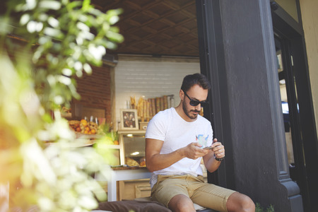restaurateur: Young male millionaire in stylish sunglasses chatting on his smart phone while sitting near own new healthy cafe with natural food, man host of small bakery reading text message during work break