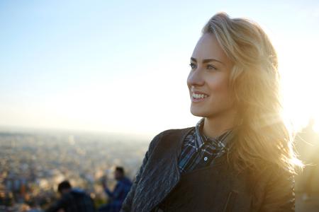 buen vivir: Mujer atractiva con buen estado de ánimo disfrutar de hermosas vistas de la ciudad mientras está de pie sobre un tejado de un edificio de alta, preciosa hembra sonriente que se relaja después de caminar por la calle en cálido día de primavera en el tiempo libre