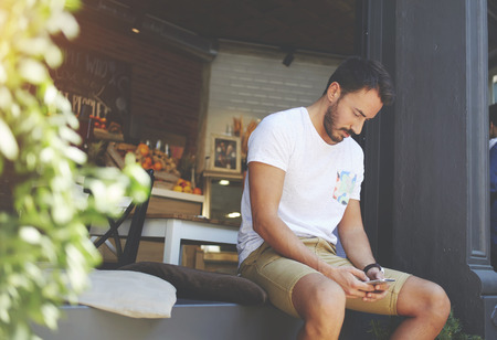 restaurateur: Young man entrepreneur reading comments about healthy cafe on mobile phone while sitting there, male restaurateur disseminates information about own organic bar via cell telephone during work break Stock Photo