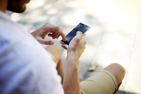 hombres jovenes: Imagen de detalle de las manos del hombre que usa el teléfono móvil con pantalla copia espacio en blanco para su mensaje publicitario de texto o contenido, tipo inconformista búsqueda de información en el teléfono celular mientras está sentado al aire libre