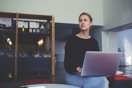 netbook: Young thoughtful businesswoman ponders something while holding on her knees open laptop computer, confident female using portable net-book while sitting in modern office cafe during work break