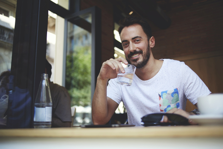 restaurateur: Smiling confident businessman holding glass of water during rest in comfortable favorite cafe, handsome male restaurateur waiting for international partners while sitting in own restaurant interior