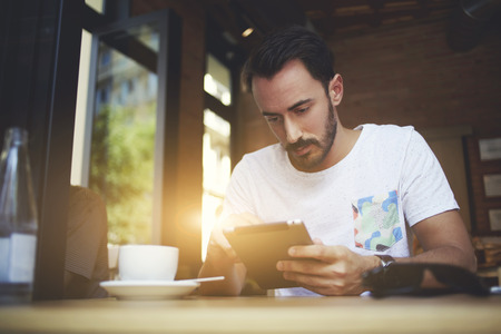 store man: Skilled man employer reviewing via digital tablet electronic resume of waiters while sitting in own coffee shop, young male student adds new applications to touch pad during lunch in coworking cafe