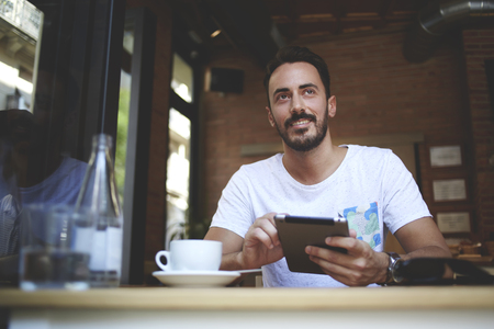 restaurateur: Male restaurateur with smile greets customers while working on digital tablet in own comfortable restaurant, joyful man entrepreneur holding touch pad while waiting for order in modern coffee shop Stock Photo
