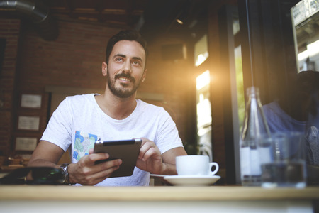 restaurateur: Happy man proprietor of cozy cafe rejoice in own success while sitting with touch pad  at dining table, smiling male holding digital tablet and thinks about something good during lunch in coffee shop Stock Photo