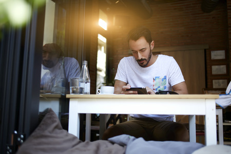 Male store manager checks  accepted products on digital tablet while sitting at dining table in modern cafe, successful businessman searching information via touch pad during work break in coffee shop