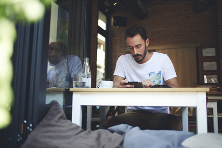 restaurateur: Young bearded man searching required information in internet via touch pad while waiting friends in coffee shop, male concentrated reading world news on digital tablet during work break in restaurant Stock Photo