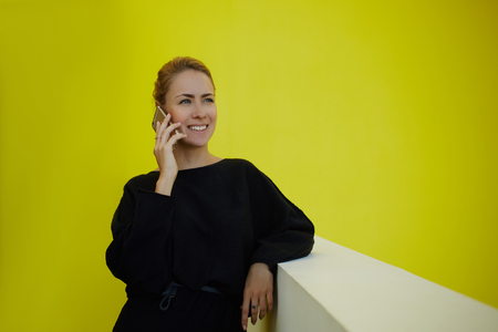 female lawyer: Smiling female lawyer talking on mobile phone after winning court case while standing in office interior, happy woman CEO calling with cell telephone to partner after successful meeting with client