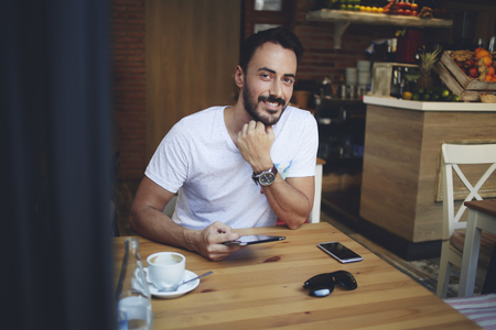 restaurateur: Smiling man owner using digital tablet for ordering new ecological products for his coffee shop, cheerful successful male sitting in restaurant with portable touch pad before meeting with investors