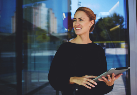 Skilled female manager hold digital tablet and smiling to someone during rest after conference, succesful smiling woman entrepreneur distracted from work on touch pad standing near company's building