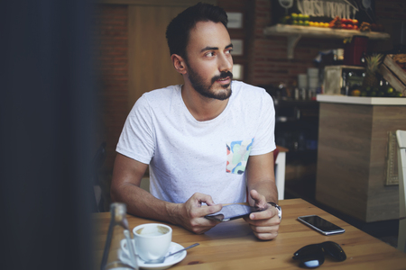 Man manager thinking about create a new menu for small luxury coffee shop while sitting with touch pad inside space, rich male holding digital tablet and looking for someone during work break in cafe