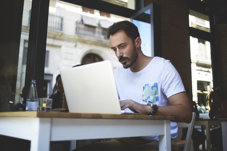 wealthy lifestyle: Man restaurant owner placing announcement in network via net-book about recruiting new personnel, male photographer searches through laptop computer in internet interesting place for shooting