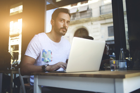 Young man professional restaurateur thinking about new ideas for create restaurant concepts on his net-book, successful businessman working on laptop computer during work break in luxury coffee shop