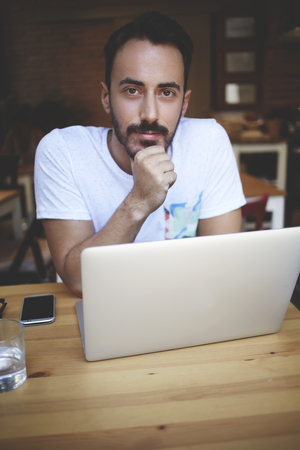 restaurateur: Young handsome man entrepreneur posing while sitting with open laptop computer in his coffee shop, confident male freelancer looking at camera during break between creating a new project on net-book Stock Photo