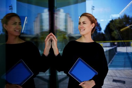 Young woman administrator holding touch pad and smiling to new clients of the hotel which she waiting outside, happy female entrepreneur with digital tablet in hand resting during work break outside