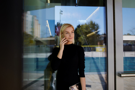 phoning: Elegant female employer phoning with cell telephone during work break outside companys building, young businesswoman talking on mobile phone with CEO while resting outdoors after big presentation Stock Photo