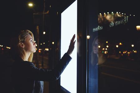 Jonge vrouw toeristische met behulp van moderne digitale display met blanco exemplaar ruimte scherm voor uw tekstbericht of inhoud, mooie vrouwelijke kijken verkeer van bussen op elektronisch prikbord in een onbekende stad