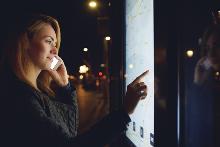 bulletin: Pretty woman tourist talking on mobile phone while looks at map of the city on electronic bulletin board, young female calling with cell telephone while touching digital display of modern bus station Stock Photo