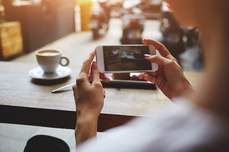 Close up of womens hands photographing sweet dessert on mobile phone for social network picture, hipster girl making photo with cell telephone camera of her morning breakfast while sitting in cafe