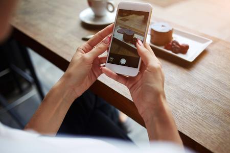 女性快適なレストランに座って携帯電話で甘いデザートの写真を作る女性の手のクローズ アップは、カフェで休憩中においしい菓子の携帯電話のカ