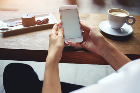 Close up of womens hands holding mobile phone with blank copy space screen for your advertising text message or promotional content, female reading news on cell telephone during rest in coffee shop Stock Photo