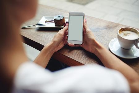 女性のクローズ アップ画像手保持携帯電話テキスト メッセージやコーヒー ショップに座って携帯電話でニュースを読んでプロモーション コンテン