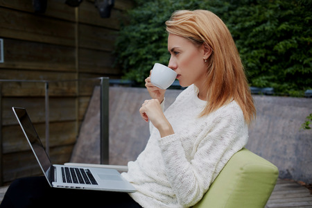 read news: Woman drinking green tea and watching movie in network via portable net-book during rest in sidewalk cafe, female enjoying coffee and read news on laptop computer while sitting in modern restaurant