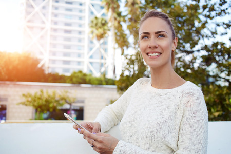 good mood: Happy beautiful woman admires something on the street while waiting for a call on cell telephone, smiling female in good mood thinking what to write on text message on mobile phone during free time Stock Photo