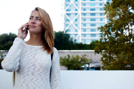 admires: Attractive female student calling via cell telephone while admires something outdoors in warm spring day, young gorgeous woman having mobile phone conversation with friend while standing in the city Stock Photo