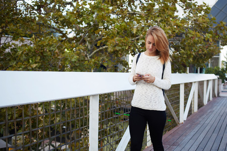 searching information: Young female student with backpack chatting on mobile phone while going on a bridge from her house to University, beautiful woman searching information via cell telephone during walking outdoors Stock Photo