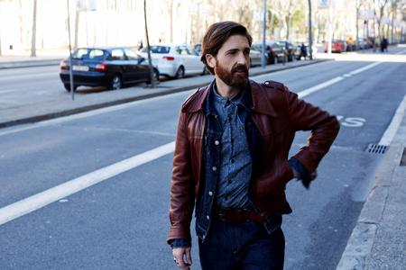 hombre con barba: hombre de la barba hermoso vestido en ropa fresca que caminan por la calle cerca de la carretera en la temporada de otoño caliente, adulto macho moderno en la chaqueta de cuero que da un paseo en la ciudad durante el tiempo de ocio los fines de semana