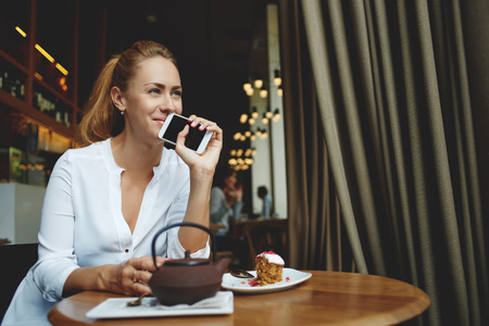 good mood: Charming woman with good mood holding mobile phone near face while relaxing in modern coffee shop interior, beautiful female dreaming about something good while waiting for a call on cell telephone