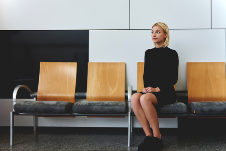 turn about: Young elegant female waiting her turn for interview with employer while sitting alone in office hallway, beautiful businesswoman thinking about ideas for information report before important conference