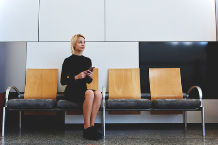telephone interview: Young thougfull woman thinking about something good while sitting on the bench in office waiting room, attractive elegant female waiting for a call on her cell telephone from employer after interview Stock Photo