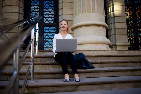 good mood: Charming woman in good mood look away while sitting with laptop computer on a stairs of a vintage building, smiling female student using portable net-book while sitting near institution or University