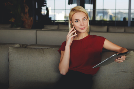 Female calling via mobile phone to her partner for tell about the monthly income results which she received via email on portable digital tablet, successful businesswoman talking on cell telephone