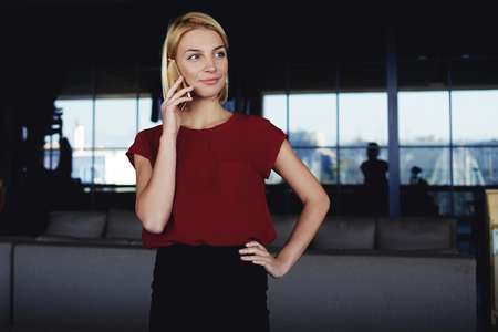 restaurateur: Successful businesswoman calling with mobile phone to her colleague which she waits in luxury restaurant interior,confident female talking on cell telephone with partner while standing in modern space