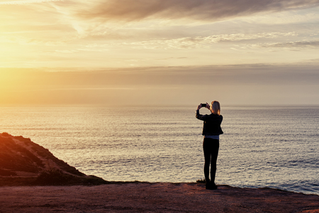 taking video: Young woman traveler shoots video on smart mobile phone of a beautiful sunset above the sea, hipster girl taking photo of amazing ocean landscape on cell telephone during her autumns adventure Stock Photo