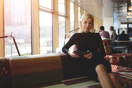 Mujer propietario de la tienda de café con la tableta digital mientras se espera para la realización de la entrevista camareros, joven empresaria descansando después de leer el libro electrónico en tableta digital durante las vacaciones de trabajo en el café