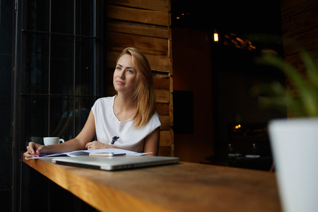 female magazine: Young charming woman dreaming about something while sitting with magazine in modern coffee shop interior, thoughtful female looking away while relaxing after work on portable computer during lunch Stock Photo