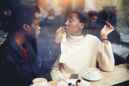 dark skinned: Dark skinned couple having lunch in cafe during recreation time, two black people in bar enjoying the time spending with each other, young man and woman relaxing in coffee shop in cold winter day