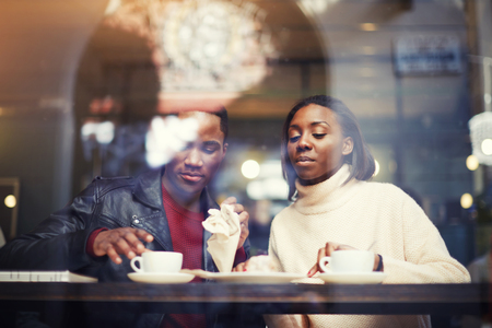 dark skinned: Dark skinned man and woman sitting together in coffee shop interior while rest after walking outdoors and drink cafe, two friends relaxing after strolling in cold winter day during weekend